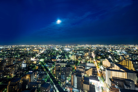 dark city: Business and culture concept for real estate and corporate construction - panoramic modern city skyline bird eye aerial night view under dramatic neon glow and beautiful dark blue sky in Tokyo, Japan