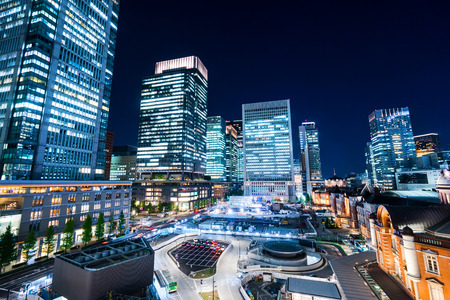 Business concept for real estate and corporate construction - panoramic modern city skyline bird eye aerial night view with tokyo station under dramatic glow and beautiful dark blue sky in Tokyo,Japan Editorial