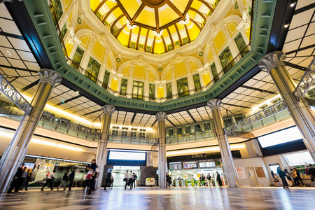 TOKYO, JAPAN - Oct.14 2016 : Business concept for real estate and corporate construction - looking up view in tokyo station with crowd of people silhouettes reflect dramatic beautiful color lights