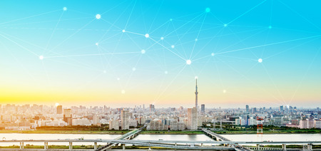 Business concept for information, communication , connection technology - panoramic modern city skyline bird eye aerial view under dramatic glow and beautiful dark blue sky