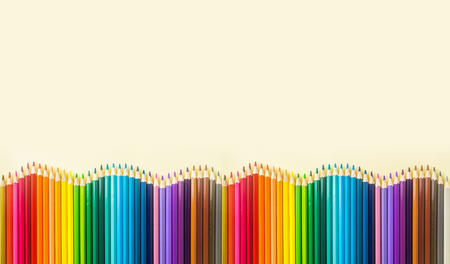 Art concept - Top view of color pencil wave on yellow paper background for mockup design