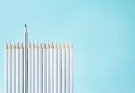 Business concept - lot of white pencils and one color pencil stand on blue paper background like fence. It's symbol of leadership, teamwork, united and communication.