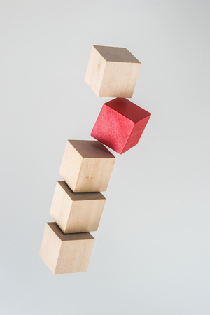 Business concept - Abstract geometric real floating wooden cube on grey background and its not 3D render. the symbol of leadership, teamwork and growth.