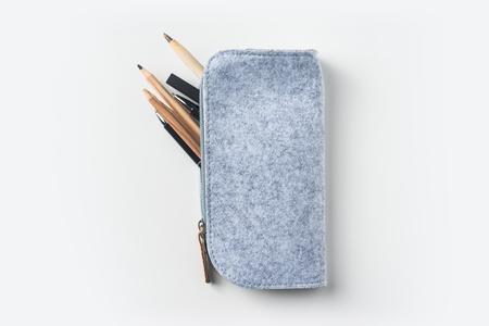 モックアップの白い背景の机の上多くのペンのグレー生地ペンシル ケースの上から見る 写真素材