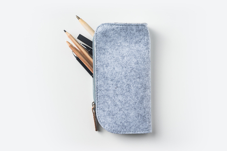 Top view of grey fabric pencil case with lot of pens on white background desk for mockup