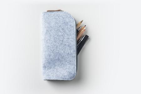 Draufsicht auf grauem Stoff Federmäppchen mit vielen Stiften auf weißem Hintergrund Schreibtisch für Mock-up