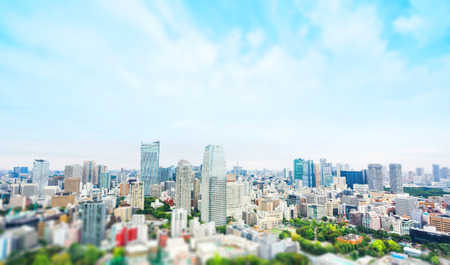 Geschäfts- und Kulturkonzept - panoramische moderne Stadtskylinevogelperspektivevogelperspektive von Tokyo-Turm unter drastischem grauem bewölktem Himmel in Tokyo, Japan. Miniatur-Tilt-Shift-Effekt