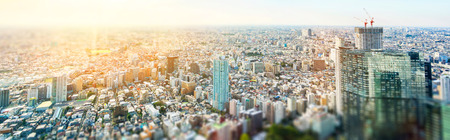 Business and culture concept - panoramic modern city skyline bird eye aerial view under dramatic sun and morning blue cloudy sky in Tokyo, Japan. Miniature Tilt-shift effect Stockfoto