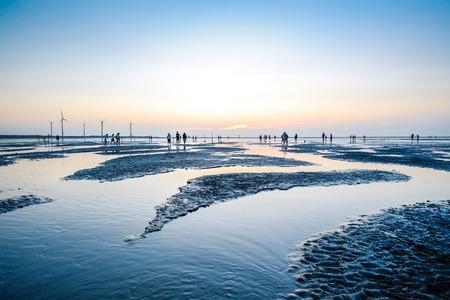 아시아 문화 - 바다 수준의 아름 다운 풍경은 판타지 극적인 일몰 하늘과 Gaomei 습지, 타이 중, 대만에서 유명한 여행 명소에서 사람들의 실루엣을 반영