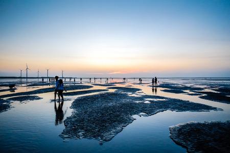 Cultura de Asia - El hermoso paisaje del nivel del mar refleja el cielo dramático de la puesta del sol de la fantasía y la silueta de la gente en los humedales de Gaomei, las atracciones famosas del viaje en Taichung, Taiwán. Foto de archivo - 85060412