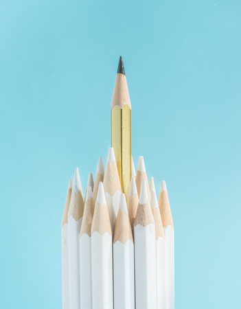 Business concept - lot of white pencils and one color pencil stand on blue paper background. It's symbol of leadership, teamwork, united and communication.