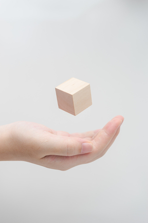 Surreal design concept - Abstract geometric real wooden cube float on girls hand with grey background.