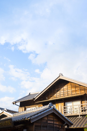 culture concept - japanese traditional historical wooden old house under golden sun and morning blue cloudy sky