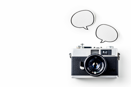Business concept - Top view of modern office desktop background with blank bubble sticker and vintage camera for mockup design and copy space isolated on white background