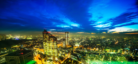 Asia Business concept for real estate and corporate construction - panoramic modern city skyline aerial night view of Shinjuku and Tokyo Metropolitan Expressway under twilight sky in Tokyo, Japan Stock Photo