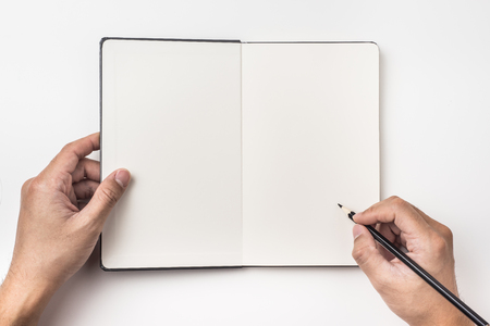 Business concept - Top view of mans hand hold black pencil above black hardcover notebook isolated on background for mockup