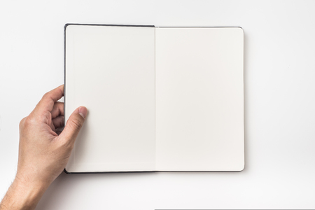 Business concept - Top view of mans hand hold black hardcover notebook isolated on background for mockup
