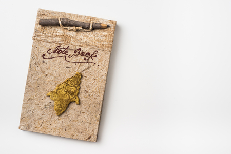 Business concept - Top view of old vintage handmade notebook isolated with wood pencil on background for mockup