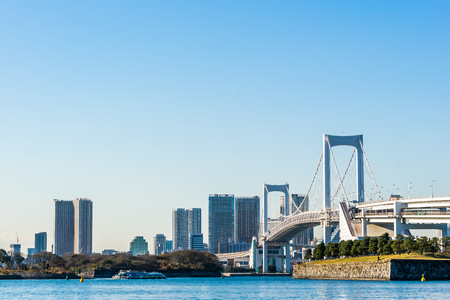 Asia Business concept for real estate and corporate construction - panoramic modern city skyline bird eye aerial view of Odaiba & rainbow bridge under bright sun and blue sky in Tokyo, Japan