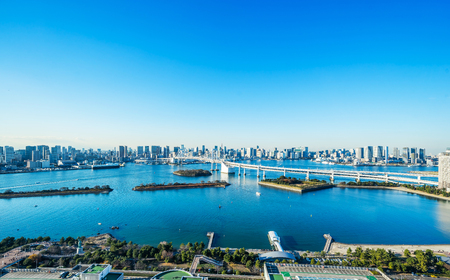 Asia Business concept for real estate and corporate construction - panoramic modern city skyline bird eye aerial view of Odaiba, tokyo tower & rainbow bridge under blue sky in Tokyo, Japan