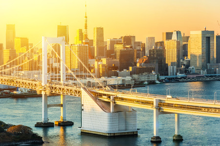 Asia Business concept for real estate and corporate construction - panoramic modern city skyline bird eye aerial view of Odaiba, tokyo tower & rainbow bridge under golden sun in Tokyo, Japan