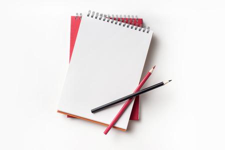 Concept de design - vue de dessus du cahier à spirale rouge et de la collection de crayons de couleur isolé sur fond blanc pour la maquette
