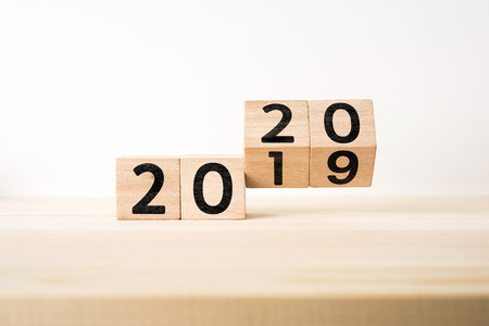 """Concepto de negocio y diseño - cubo de madera flotante geométrico abstracto surrealista con el concepto de palabra """"2020 y 2019"""" sobre piso de madera y fondo blanco"""