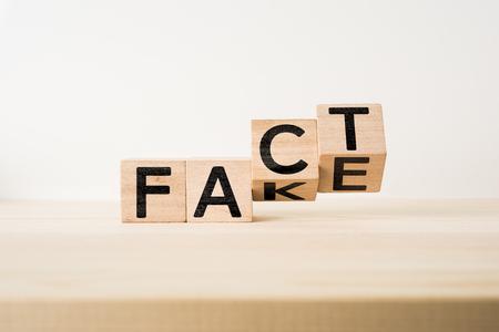 """Bedrijfs en ontwerpconcept - surreal abstracte geometrische houten kubus met woord """"FEIT & VALS"""" concept op houten vloer en witte achtergrond Stockfoto"""