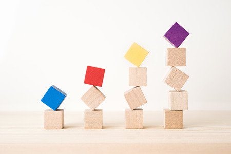 Business and design concept - abstract geometric real wooden colored cube on wooden floor background and it's not 3D render. It's the symbol of economy  growth Stockfoto
