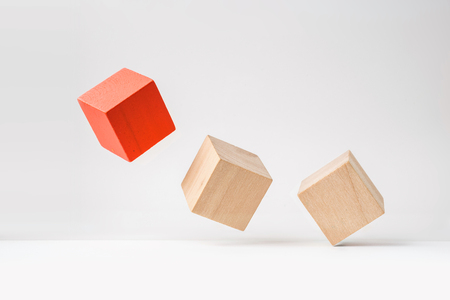 Business and design concept - abstract geometric real wooden cube with surreal layout on white floor background and its not 3D render. Its the symbol of leadership, teamwork and growth Stock Photo