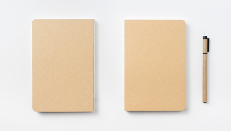 Design concept - Top view of hardcover kraft notebook and ballpoint pen isolated on white background for mockup