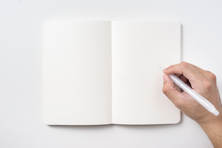 Design concept - Top view of notebook blank page and mans hand holding ballpoint pen isolated on white background for mockup
