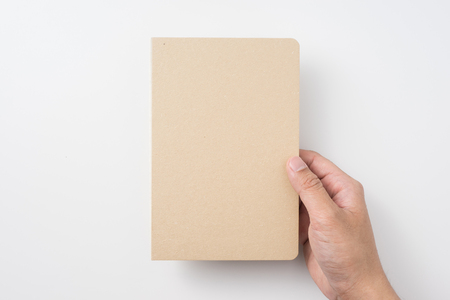 Design concept - Top view of mans hand holding hardcover kraft notebook isolated on white background for mockup
