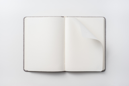 Design concept - Top view of hardcover gray linen notebook with curl blank page isolated on white background for mockup