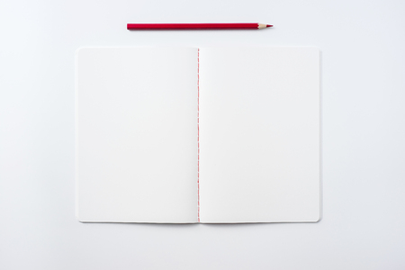 Design concept - Top view of notebook blank page and red pencil isolated on white background for mockup