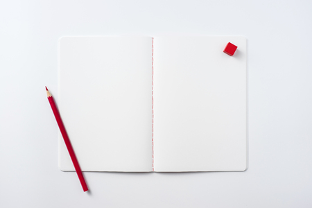 Design concept - Top view of notebook blank page, red pencil and wood cube isolated on white background for mockup