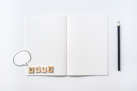 Design concept - Top view of notebook blank page, black pencil and wood cube isolated on white background for mockup