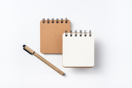 Design concept - Top view of spiral kraft notebook and ballpoint pen isolated on white background for mockup