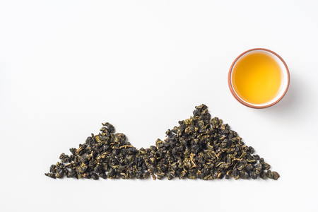 Asia culture and design concept - fresh taiwan oolong tea dry bud and chinese porcelain teacup layout like mountain & sun Stock Photo