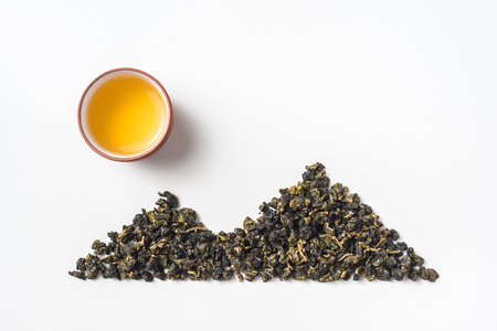 Asia culture and design concept - fresh taiwan oolong tea dry bud and chinese porcelain teacup layout like mountain & sun Фото со стока