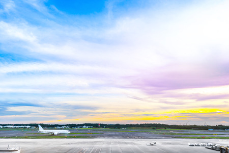 panoramic view of apron and airplane on runway under dramatic sunset & cloud sky Stock Photo
