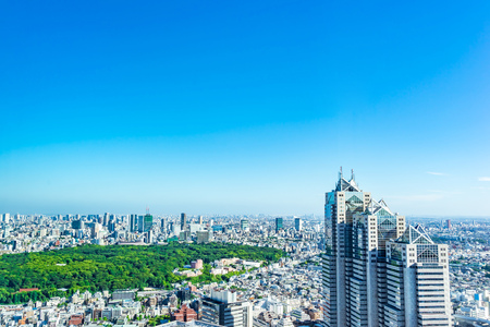 Asia Business concept for real estate and corporate construction - panoramic modern city skyline aerial view of shinjuku area under bright blue sky and sun in Tokyo, Japan 스톡 콘텐츠