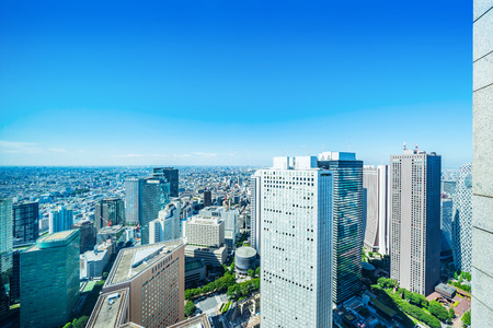Asia Business concept for real estate and corporate construction - panoramic modern city skyline aerial view of shinjuku area under bright blue sky and sun in Tokyo, Japan Stock Photo