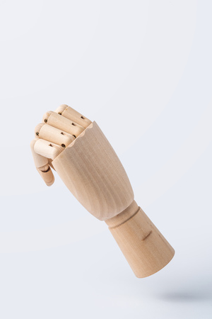 Business and design concept - wooden raise hand with fist posture isolated on white background 免版税图像