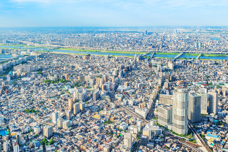 Asia Business concept for real estate and corporate construction - panoramic modern city urban skyline bird eye aerial view under sun and blue sky in koto district, Tokyo, Japan
