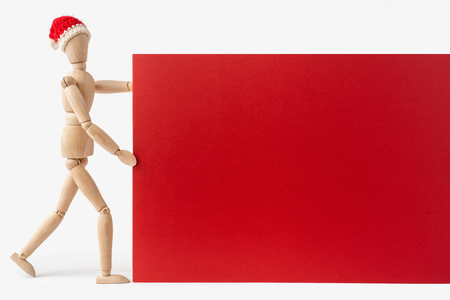holiday and design concept - wooden mannequin red hat and gift bag like santa claus hold empty red board isolated on white background