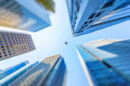 Asia Business concept for real estate and corporate construction - looking up view of modern city skyline with airplane in tokyo, japan with tilt shift, miniature, blur effect 版權商用圖片