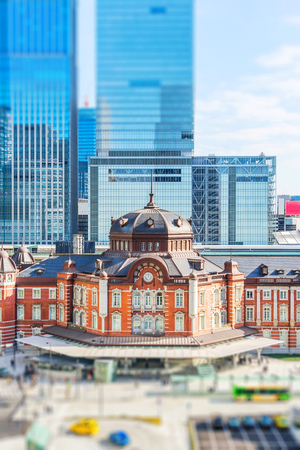 Asia business concept for real estate and corporate construction - panoramic city skyline aerial view under blue sky  and sun of tokyo station, Japan with tilt shift, miniature, blur effect