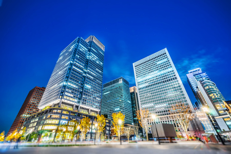 Asia Business concept for real estate and corporate construction - looking up view of panoramic urban city skyline view under blue night in tokyo, Japan with tilt shift, miniature, blur effect
