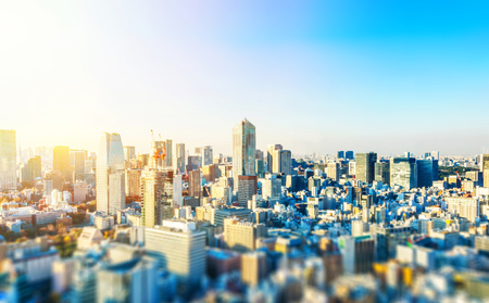 Asia business concept for real estate and corporate construction - panoramic city skyline aerial view under blue sky and sun in Tokyo, Japan with tilt shift, miniature, blur effect